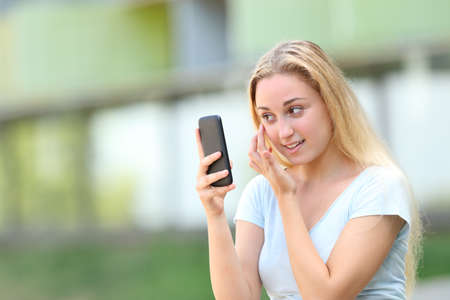 Teenage girl using smart phone as a mirror outdoors in an university campus