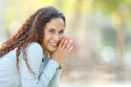 Portrait of a happy mixed race woman posing looking at camera sitting in a park Stock Photo