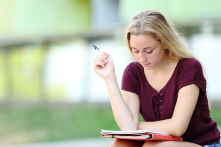 Studious student studying memorizing paper notes sitting in a campus Stockfoto