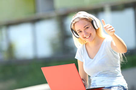 Happy student e-learning gesturing thumbs up sitting outdoors in an university campus Stock Photo