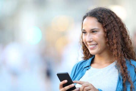 Happy mixed race woman looking away holding smart phone walking in the street