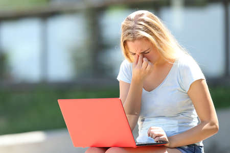 Student with eyesight problems suffering eyestrain outdoors in an university campus 写真素材