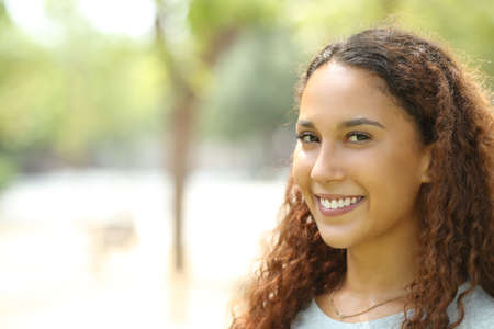 Beauty mixed race woman posing looking at camera with perfect smile in a park