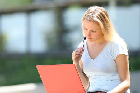Konzentriertes E-Learning für Studenten mit einem roten Laptop im Freien auf einem Campus