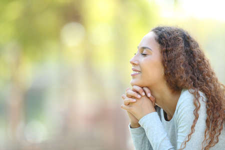 Side view portrait of a happy mixed race woman meditating and breathing fresh air outdoors in a park Standard-Bild