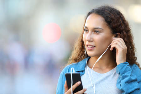 Mixed race woman holding smart phone putting earphones listening to music looking at side walking in the street