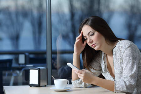 Worried girl checking phone message sitting in a coffee shop in a sad day