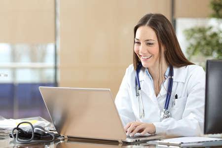 Glücklicher Arzt mit einem Laptop beim Schreiben von Inhalten bei der Konsultation