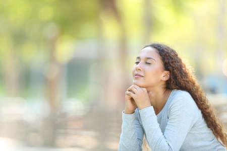 Mixed-Race-Frau entspannt beim Meditieren im Freien in einem Park Standard-Bild