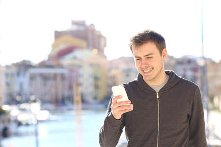 Happy man uses a smart phone walking on vacation in a coast town