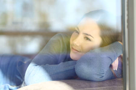 Relaxed woman looks through a window sitting on a sofa in the living room at home Stock Photo