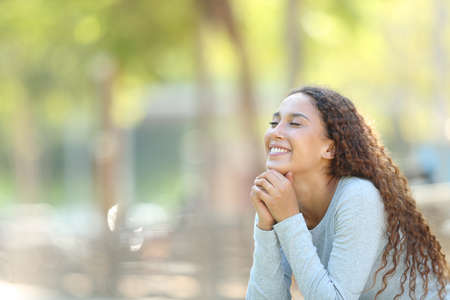 Happy mixed-race woman meditating sitting in a park with copy space