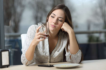 Front view portrait of a worried pensive woman looking at empty glass sitting in a coffee in a winter evening Stock Photo