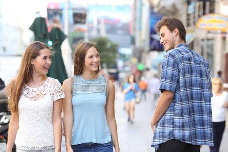 Glücklicher Mann, der mit den glücklichen Frauen flirtet, die auf der Straße spazieren gehen Standard-Bild