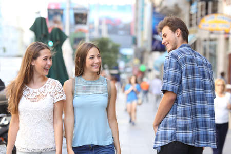 Happy man flirting with tho happy women walking in the street Foto de archivo