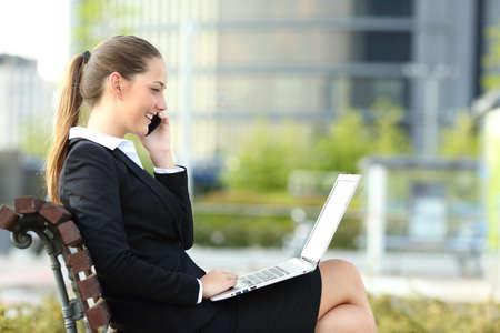 Side view portrait of a happy businesswoman talking on phone and checking laptop sitting on a bench