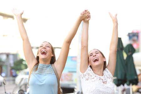 Deux amis enthousiastes célébrant le succès en levant les bras ensemble à l'extérieur dans la rue