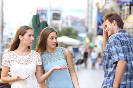 Man flirting being rejected by disappointed women walking in the street