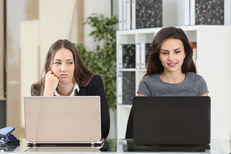 Vista frontale di un'impiegata invidiosa che guarda il suo collega che lavora accanto