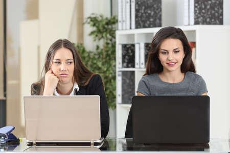 Widok z przodu zazdrosnego pracownika patrzącego na swojego kolegi pracującego obok