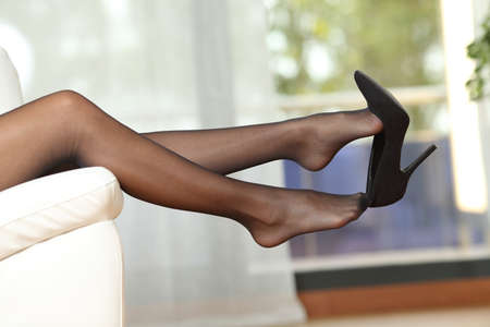 Side view portrait of a beauty woman legs with nylons taking off shoes lying on a couch at home Banque d'images