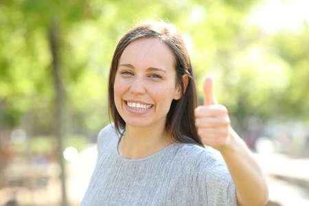 Mujer feliz mira a la cámara con los pulgares para arriba de pie al aire libre en un parque