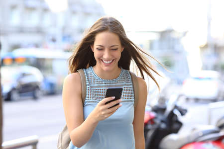 Front view portrait of a happy woman laughing walking towards camera  watching smart phone content in the street Stock fotó