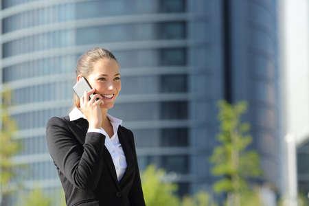 Feliz empresaria hablando por teléfono y caminando en la calle Foto de archivo