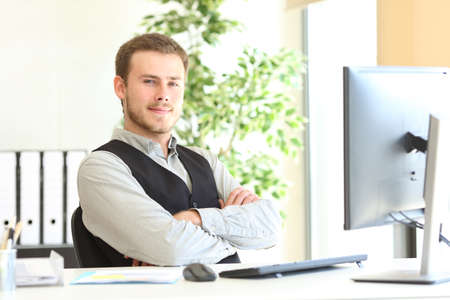 Confident executive posing looking at camera folding arms at office