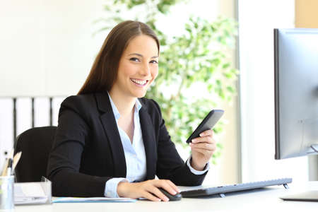 Happy businesswoman posing looking at camera holding smart phone at office Archivio Fotografico - 131834653