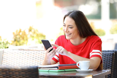 Happy student in red browsing phone content sitting in a coffee shop terrace