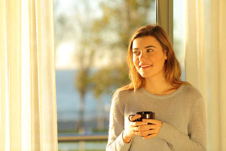 Front view portrait of a happy teen holding coffee mug looking at side beside a window at home
