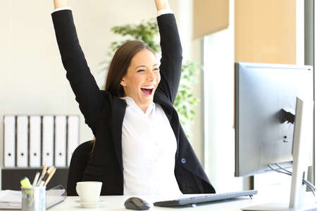 Excited businesswoman checking good news on computer celebrating success at office Stock Photo