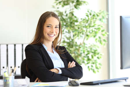 Happy businesswoman wearing suit posing sitting looking at camera at office Archivio Fotografico - 131834667