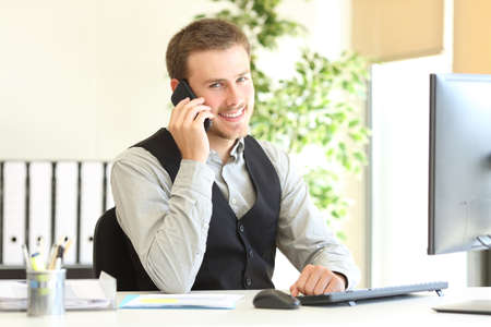 Happy executive talking on phone looking at camera sitting at office
