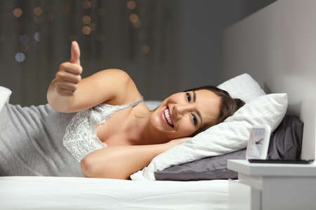 Happy hotel guest gesturing thumbs up lying on a bed in the night