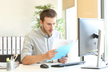 Shocked businessman checking documents with bad news at office Banco de Imagens