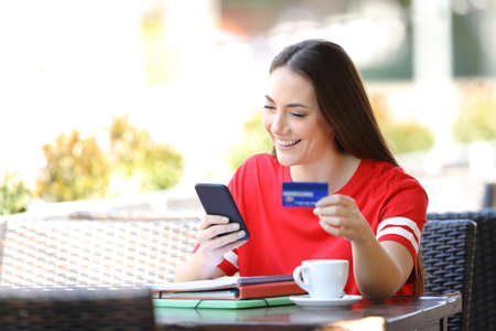 Happy student in red paying online with credit card sitting in a coffee shop terrace