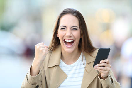 Front view portrait of excited woman holding smart phone looking at camera in the street