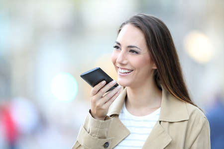 Happy casual woman using voice recognition on cell phone to record a message in the street