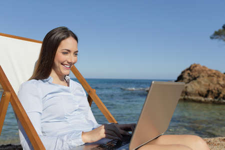 Happy entrepreneur using laptop sitting on a deck chair on vacation on the beach Stock fotó