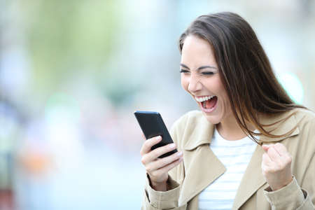 Excited woman finds good on line offers on smart phone standing in the street Stock fotó