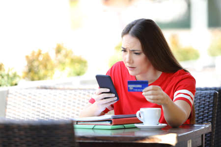 Worried student paying online with credit card sitting in a coffee shop terrace Stock Photo