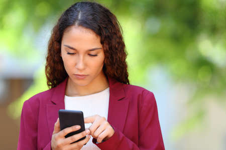 Front view portrait of a serious mixed race woman using smart phone on green background Stock fotó