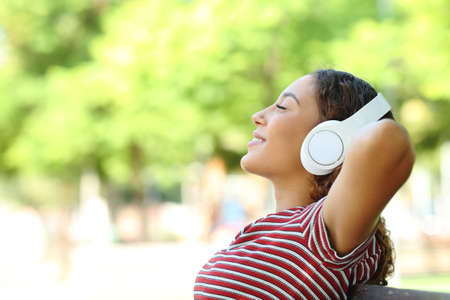 Side view portrait of a happy mixed race woman listening to music resting sitting on a bench in a park