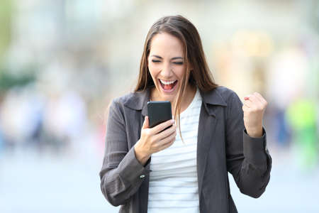 Front view portrait of excited woman checking smart phone on line content in the street