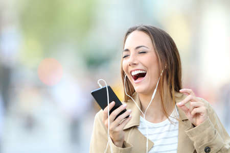 Funny girl wearing earphones listening to music and singing holding smart phone in the street