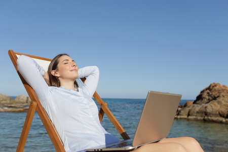 Relaxed entrepreneur resting sitting on a deck chair on the beach with a laptop on legs