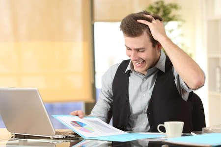 Excited businessman checking statistics on paper document at office