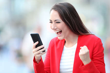 Excited lady in red celebrating good news checking smart phone on line content in the street Stock Photo